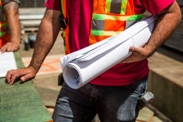 Person holding construction papers